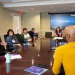 8 people gathered around a meeting room table in conversation